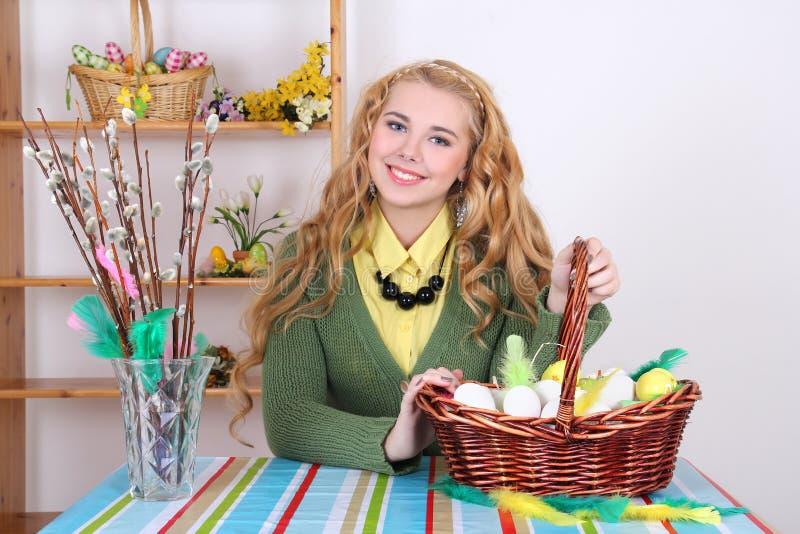 Attraktivt blont, korg med easter ägg och pussy-pil royaltyfri fotografi