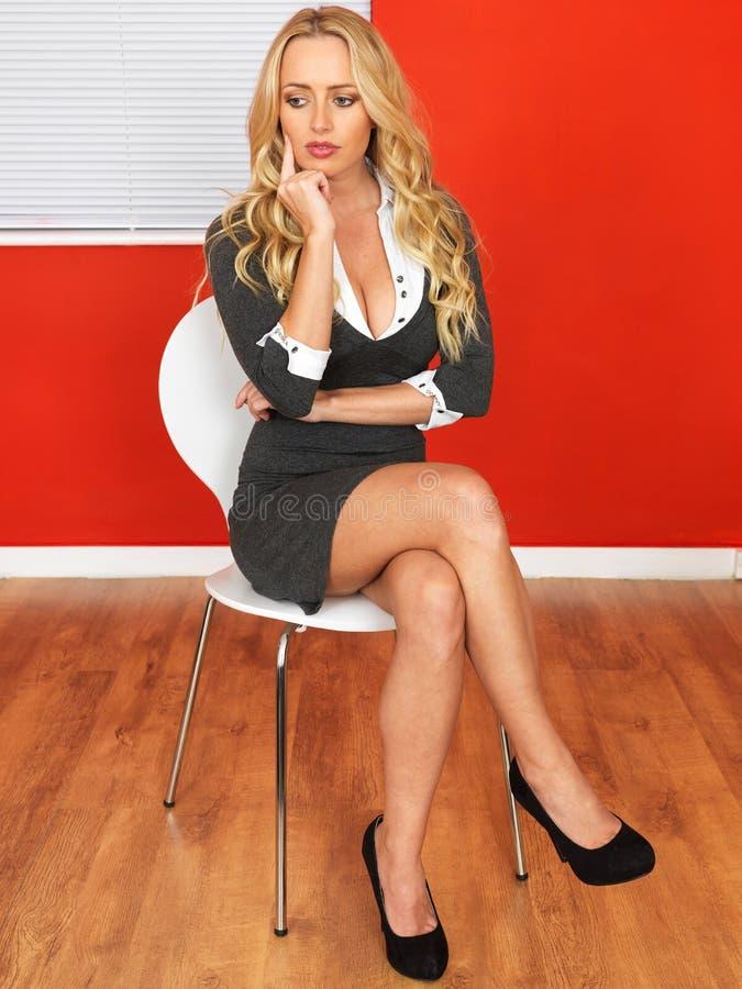 Attraktivt fundersamt sammanträde för affärskvinna i en stol arkivfoto