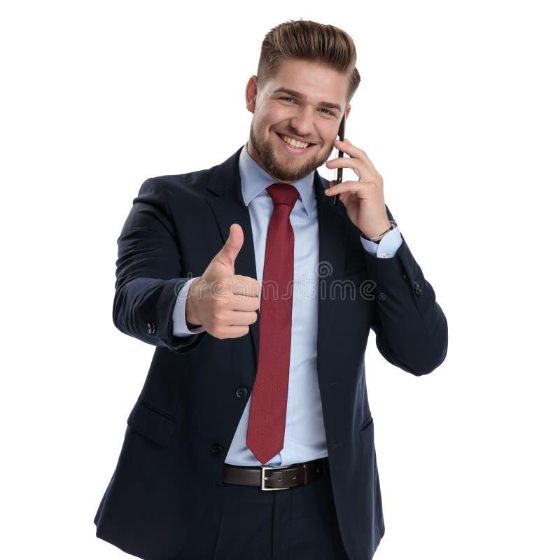 Attraktivt göra en gest för affärsman som är ok, och samtal på hans telefon fotografering för bildbyråer