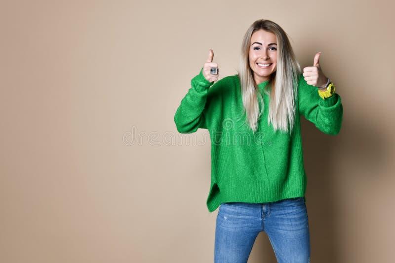 Attraktivt ge sig för ung kvinna tummar upp gest av godkännande och framgång med ett stråla leende royaltyfri foto