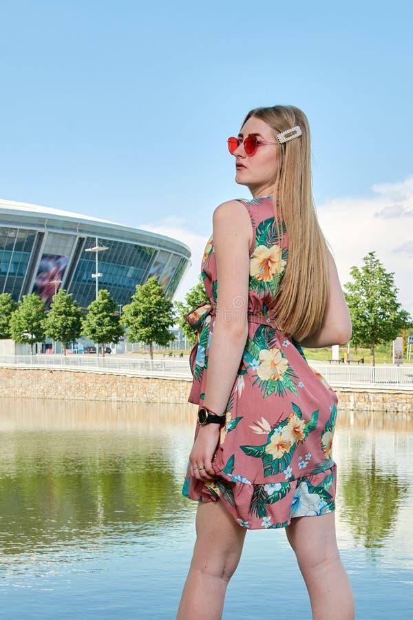 attraktivt kvinnabarn Röd solglasögon, färgklänning St?ende f?r flicka` s Fotbollsarenabakgrund royaltyfri bild