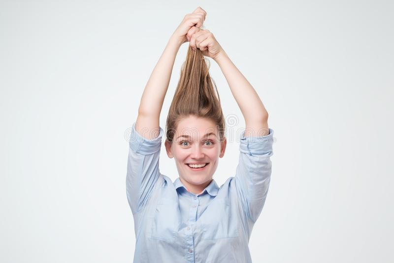 Attraktivt kvinnainnehav honom länge hår upp arkivfoto