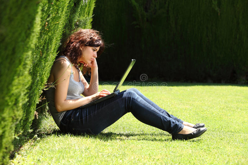 Attraktivt kvinnasammanträde på gräset i en parkera borrade med en bärbar dator royaltyfri fotografi