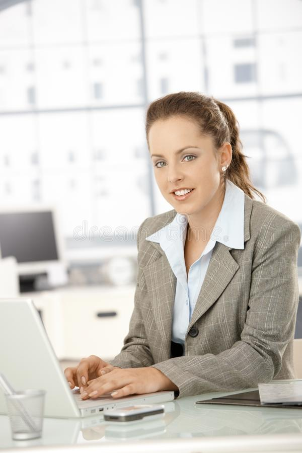 Attraktivt kvinnligt arbete på bärbara datorn i regeringsställning royaltyfria bilder