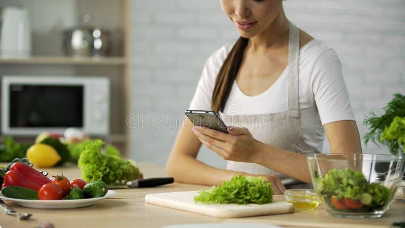 Attraktivt kvinnligt sammanträde på tabellen och läs- salladrecept på mobiltelefonen royaltyfria foton