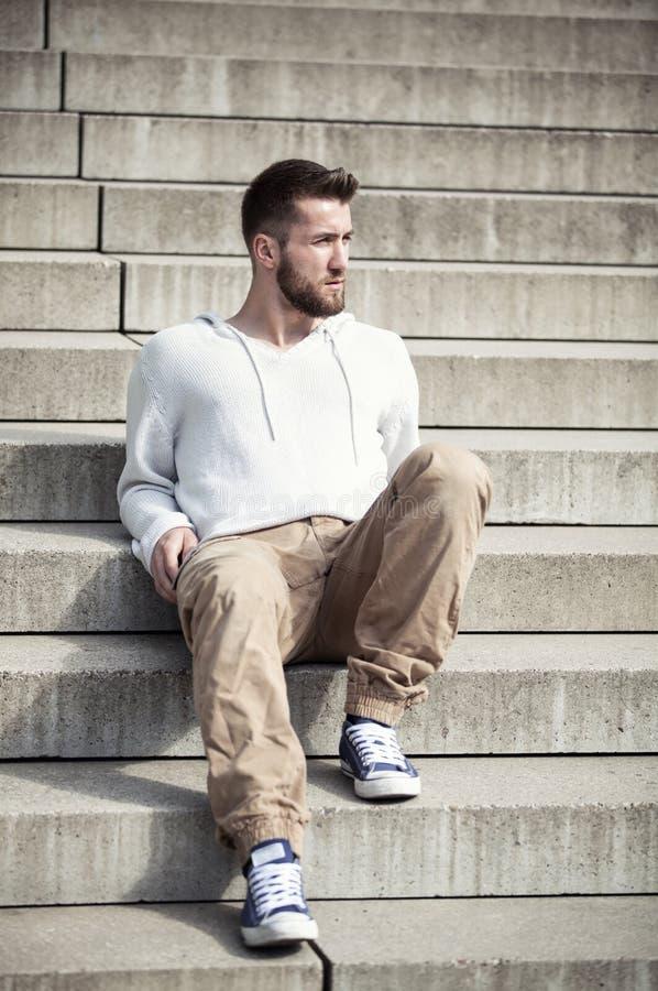 Attraktivt mansammanträde på trappa fotografering för bildbyråer
