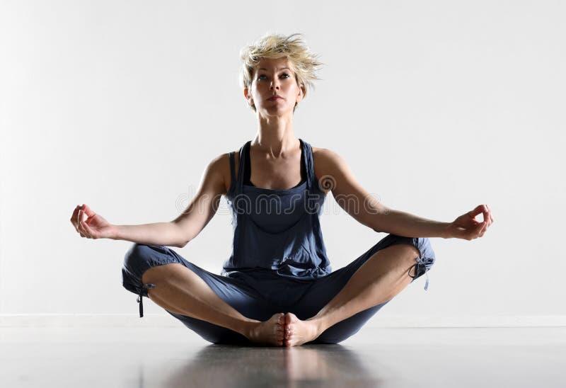 Attraktivt meditera för sammanträde för ung kvinna royaltyfri foto