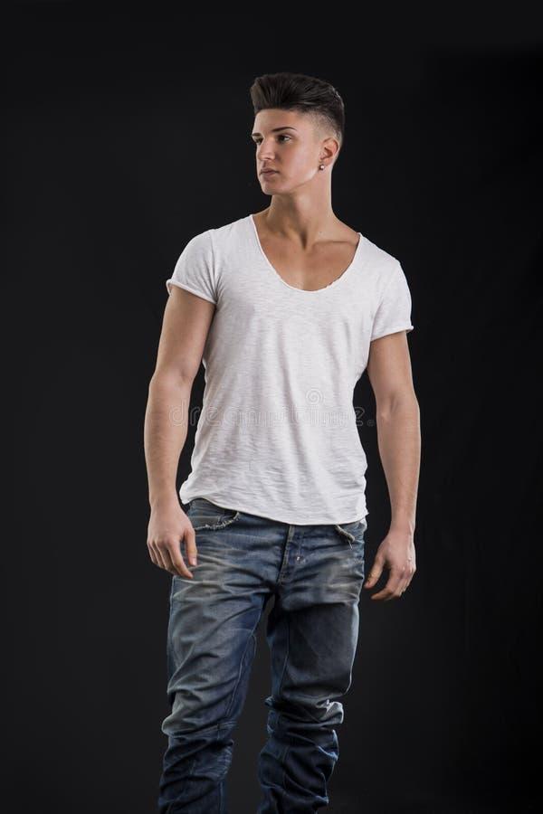 Attraktivt moderiktigt anseende för ung man på svart bakgrund arkivfoton