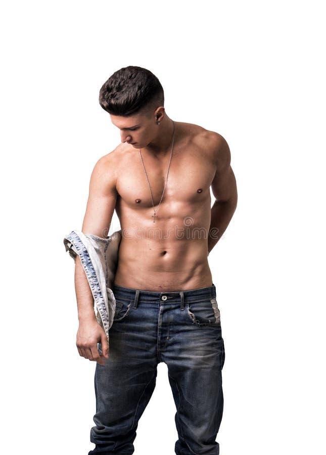 Attraktivt moderiktigt klä av för ung man som av tar skjortan arkivfoto