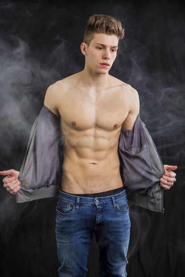 Attraktivt muskulöst moderiktigt klä av för ung man arkivbild