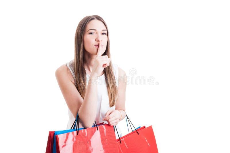 Attraktivt nätt shopaholic med shoppingpåsar som gör en tystnad royaltyfri bild