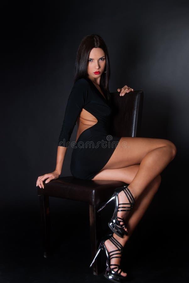 Attraktivt sammanträde för klänning för brunettklädersvart på läderstol royaltyfri bild