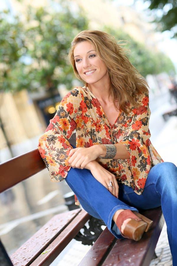 Attraktivt sammanträde för trendig kvinna på offentlig bänk fotografering för bildbyråer