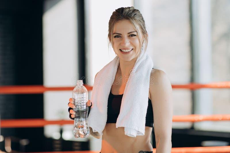 Attraktivt sportflickale och dricksvatten, medan stå i konditiongrupp royaltyfri fotografi