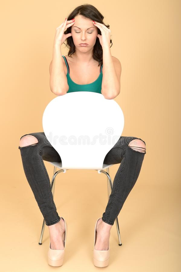 Attraktivt stressat frustrerat uttråkat sammanträde för ung kvinna på en vit stol arkivbild
