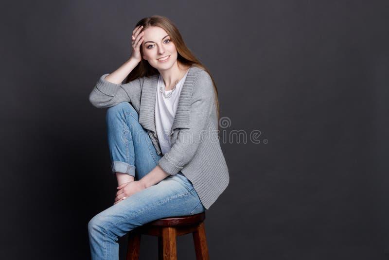 Attraktivt ung flickasammanträde på hög trästol Hon ler uppriktigt royaltyfri fotografi