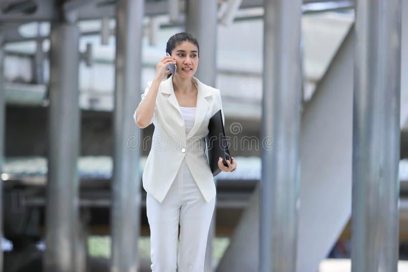 Attraktivt ungt asiatiskt samtal för affärskvinna på telefonen under att gå till kontoret arkivbilder