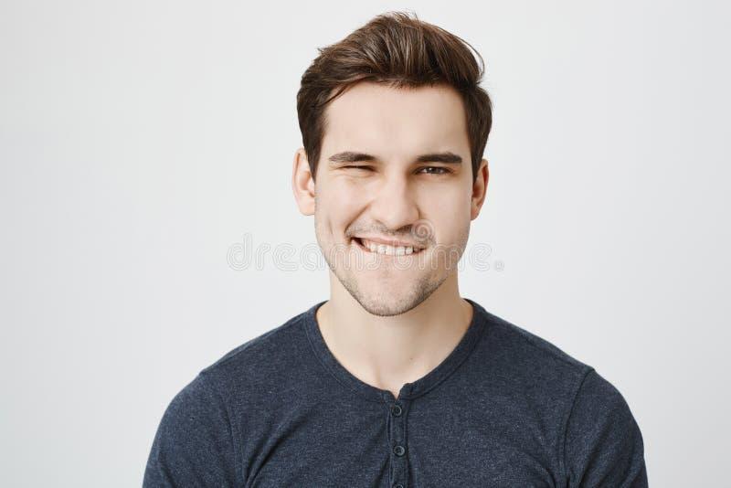 Attraktivt ungt macho blinka och bita hans kant som flörtar med någon, medan stå över grå bakgrund varmt royaltyfri bild
