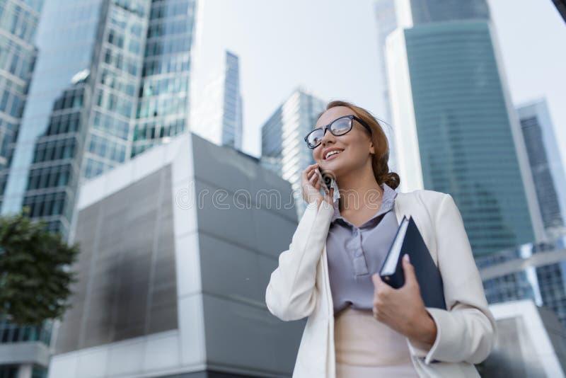 Attraktivt ungt samtal för affärskvinna på telefonen under att gå till kontoret fotografering för bildbyråer