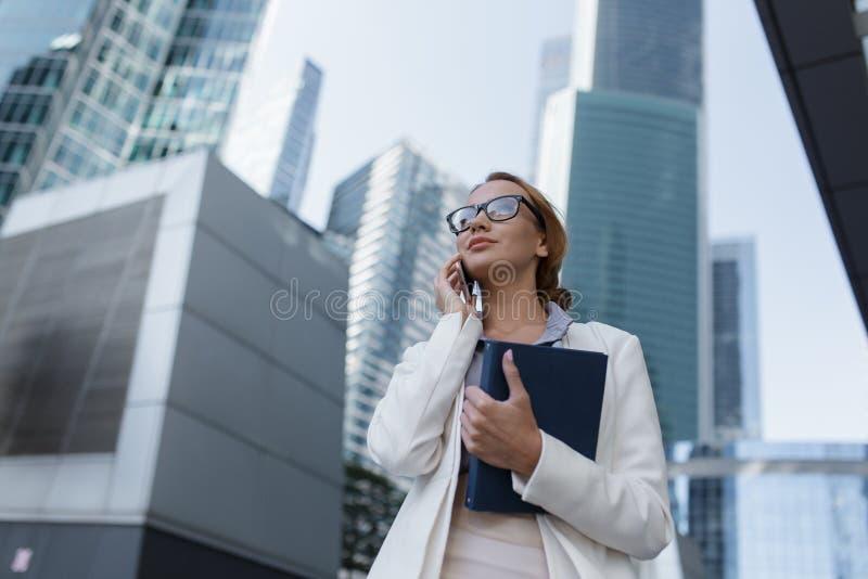 Attraktivt ungt samtal f?r aff?rskvinna p? telefonen under att g? till kontoret arkivbilder