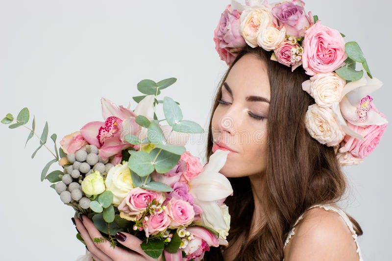 Attrative tender woman in roses wreath smelling bouquet of flowers royalty free stock photo