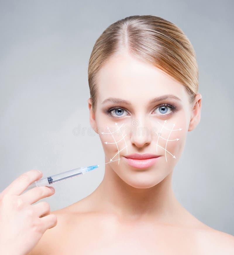 Attrative ung kvinna som injicerar behandling in i hud arkivfoto