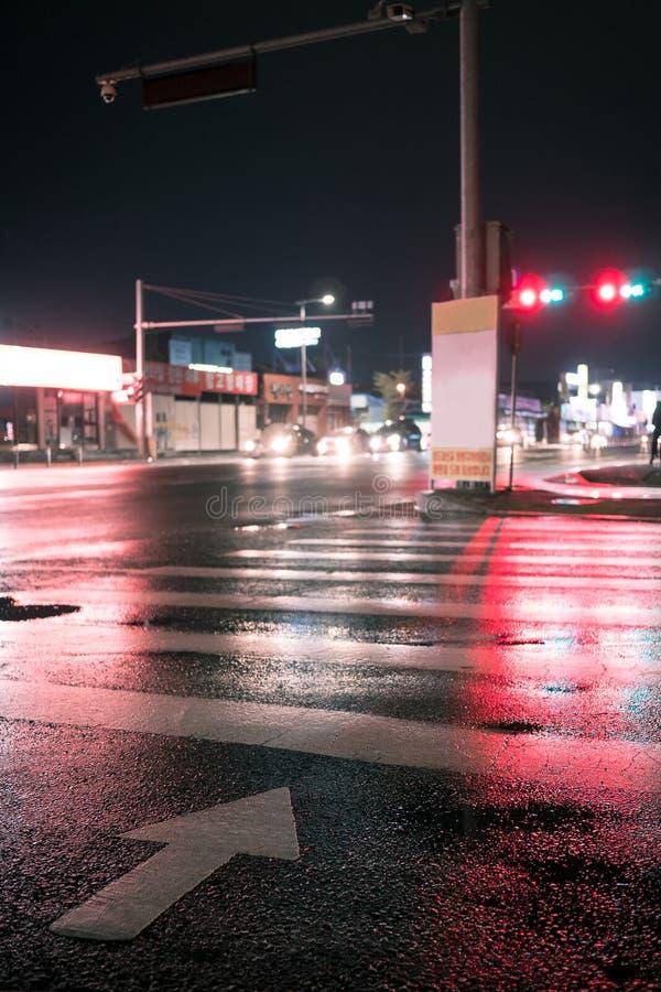 Attraversamento con indicare freccia nella notte alla luce al neon fotografia stock