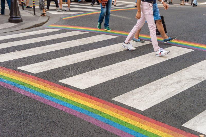 Attraversamento della bandiera di gay pride nel villaggio gay di Parigi con l'attraversamento della gente fotografia stock