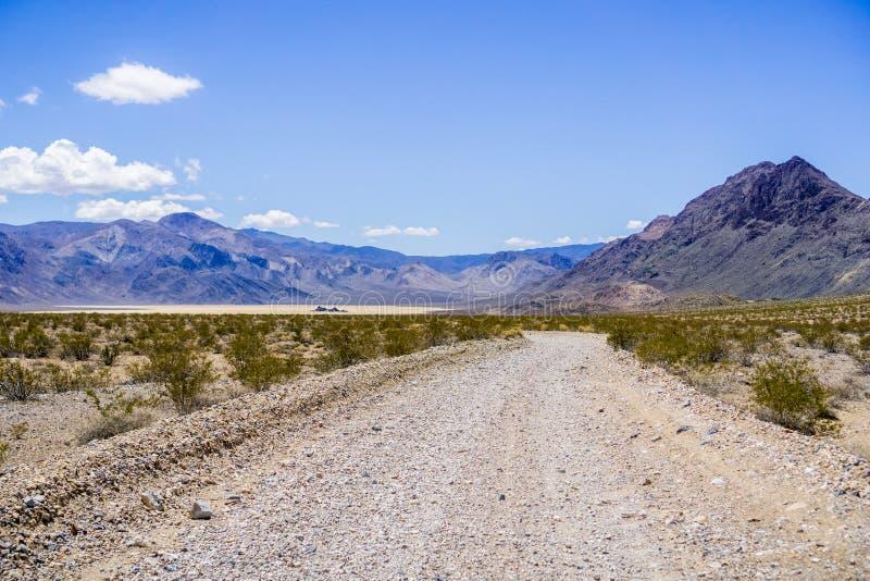 Attraversando su una strada non pavimentata through una regione isolata di parco nazionale di Death Valley; Pista Playa, montagne fotografie stock libere da diritti