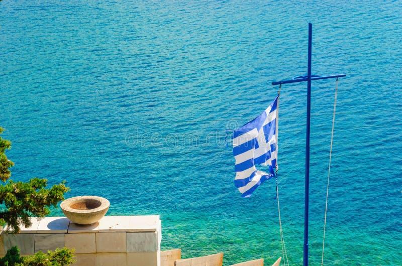 Attraversi con la bandiera ed il mare greci, isola del mar Egeo fotografie stock