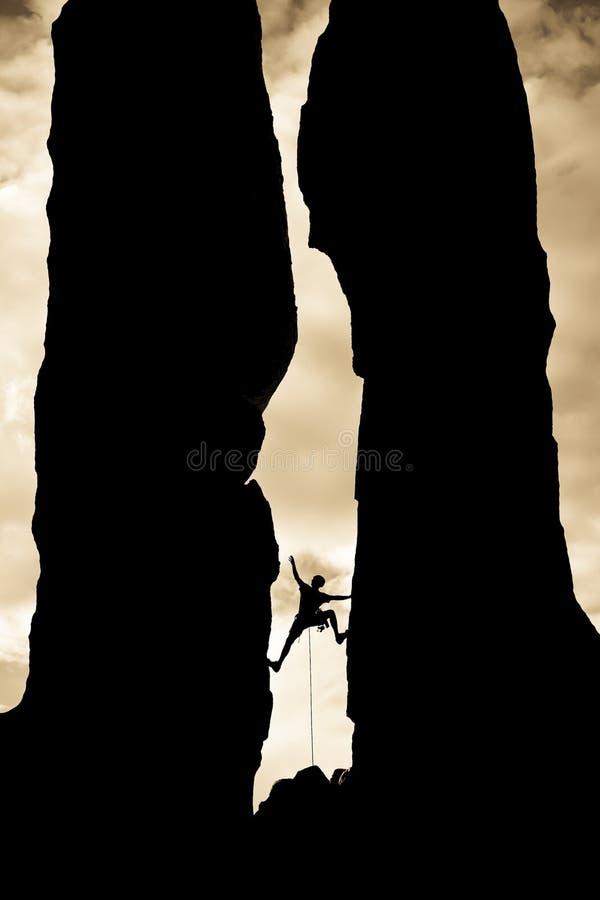 attraverso lo spacco dello scalatore che raggiunge roccia fotografia stock