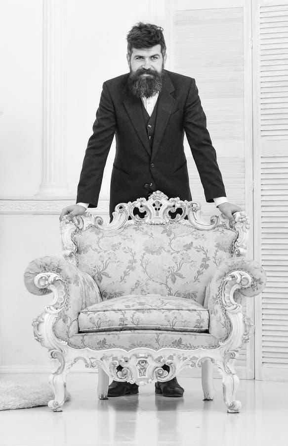 Attrayant et élégant machos sur sourire, maigre réfléchi de visage sur le fauteuil démodé concept de mode et de style Homme photo stock