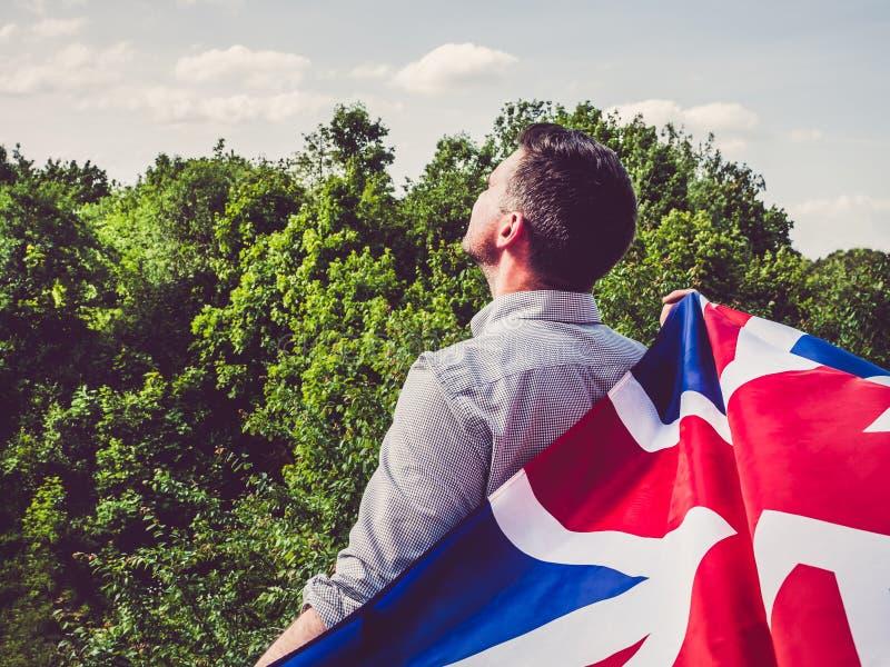Attrayant, jeune homme ondulant un drapeau britannique image stock