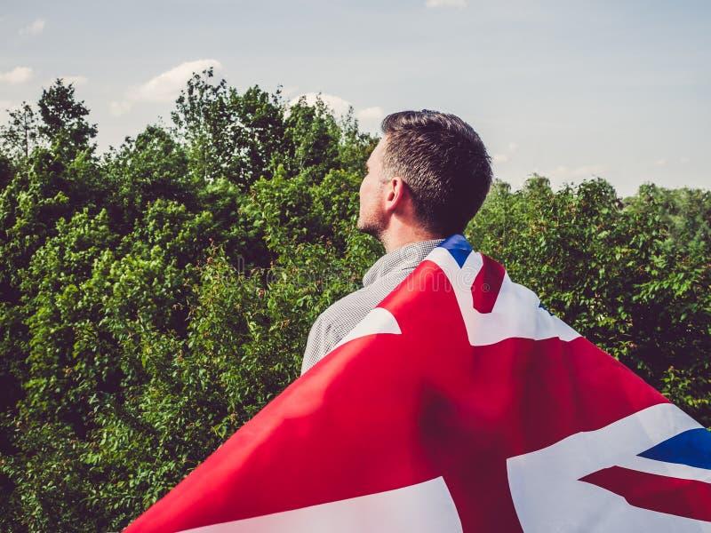 Attrayant, jeune homme ondulant un drapeau britannique image libre de droits