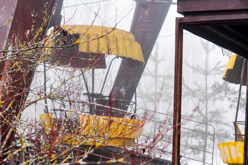 Attrazione gialla della ruota di ferris della ruggine in nebbia nella zona di Cernobyl del parco di divertimenti abbandonata inve immagine stock libera da diritti