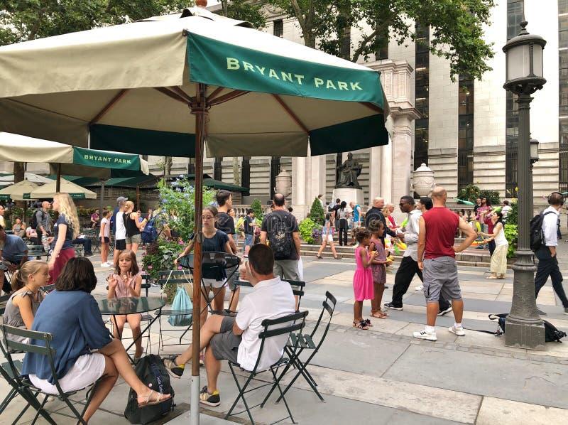 Attrazione turistica e la gente di Bryant Park New York City divertendosi la destinazione della famiglia fotografia stock