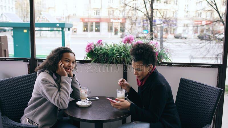 Attrcative mieszał biegowego kobiety obsiadanie przy stołem w ulicznym cukiernianym opowiada telefonie komórkowym podczas gdy jej obrazy royalty free