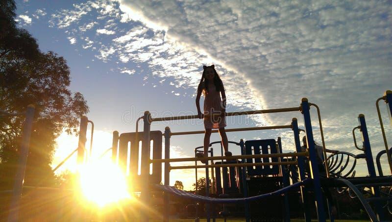 Attrezzatura climibing del campo da giuoco della ragazza come il sole sta mettendo immagini stock