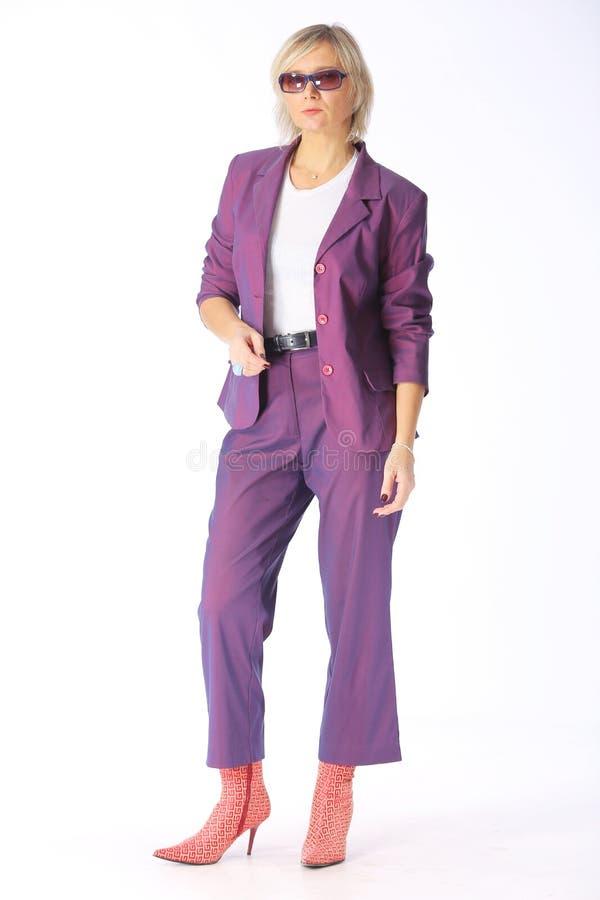 Attrezzatura della primavera, ritratto di giovane donna bionda moderna in un pantsuit lilla porpora e stivali con i talloni, colp fotografia stock