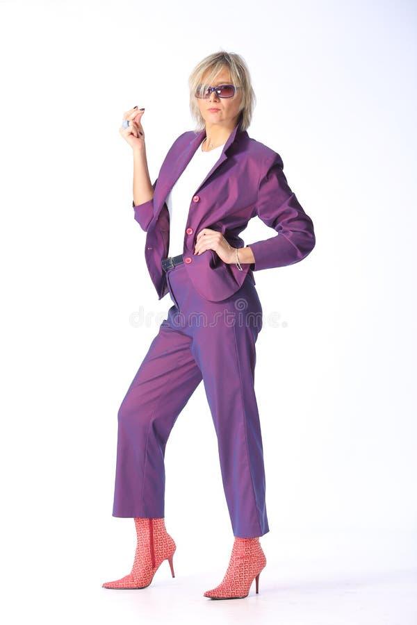 Attrezzatura della primavera, ritratto di giovane donna bionda moderna in un pantsuit lilla porpora e stivali con i talloni, colp fotografia stock libera da diritti