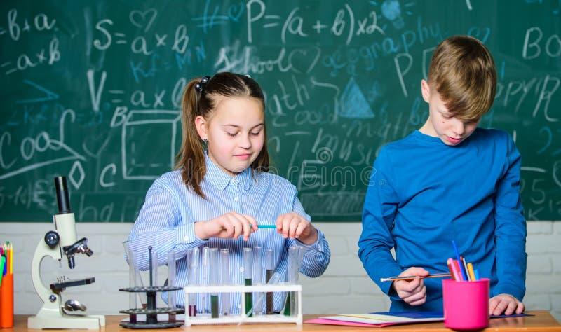Attrezzatura di biologia Bambini felici Lezione di biologia studenti che fanno gli esperimenti di biologia con il microscopio in  immagini stock