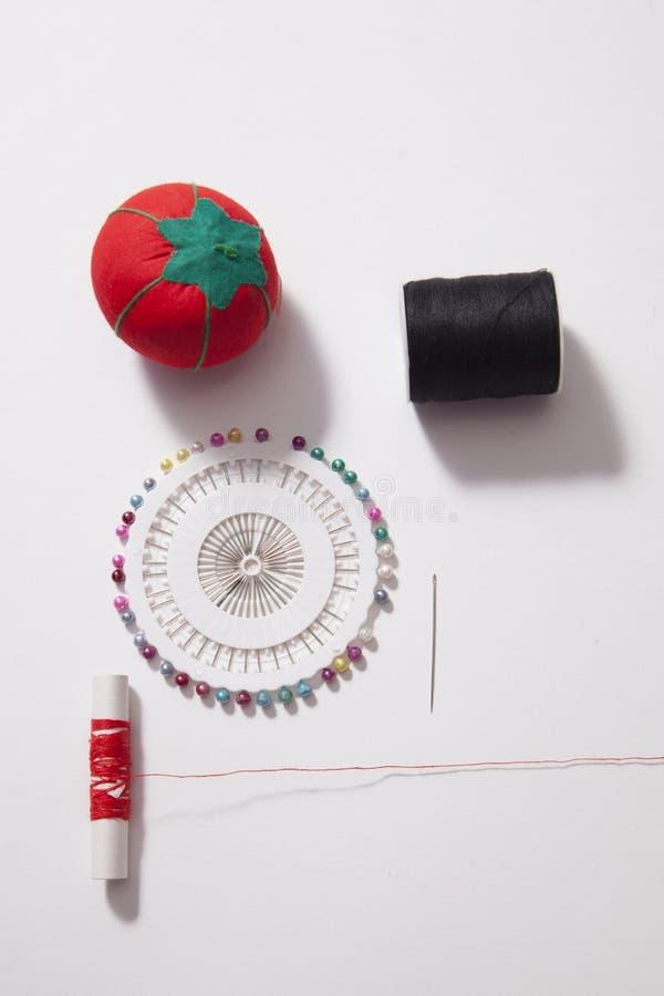 Attrezzatura di cucito con il puntaspilli ed ago e filo rosso fotografia stock libera da diritti