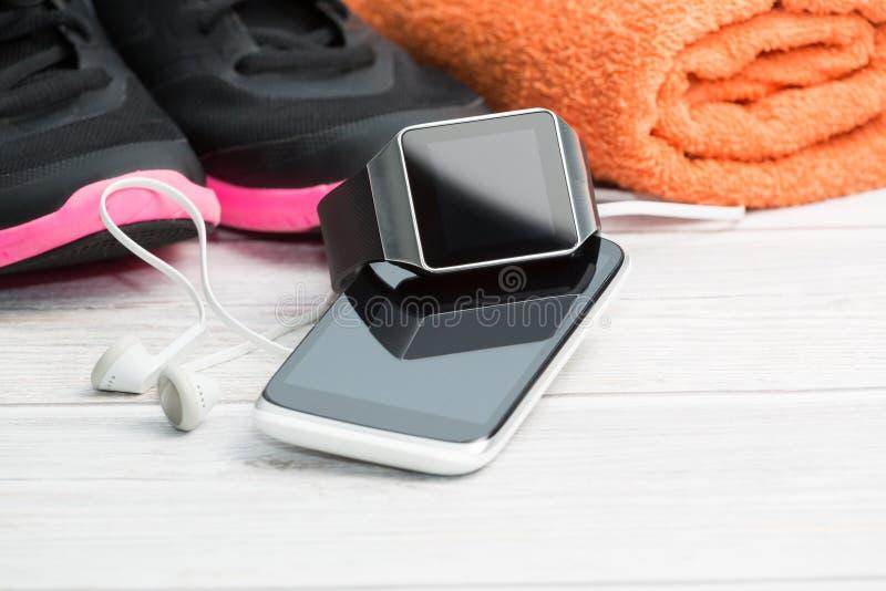 Attrezzatura di forma fisica, orologio astuto e telefono fotografia stock