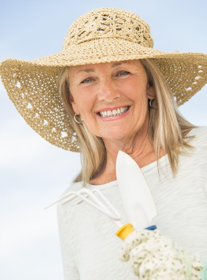 Attrezzatura di giardinaggio sorridente della tenuta della donna contro il cielo fotografie stock libere da diritti