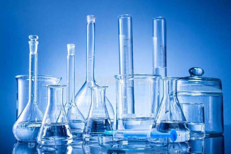 Attrezzatura di laboratorio, bottiglie, boccette su fondo blu fotografia stock
