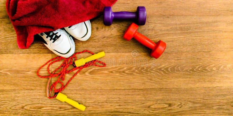 Attrezzatura di sport, corda, forma fisica, palla, sport, asciugamano, scarpe da tennis, pavimento di legno, scarpe da corsa, tes immagine stock