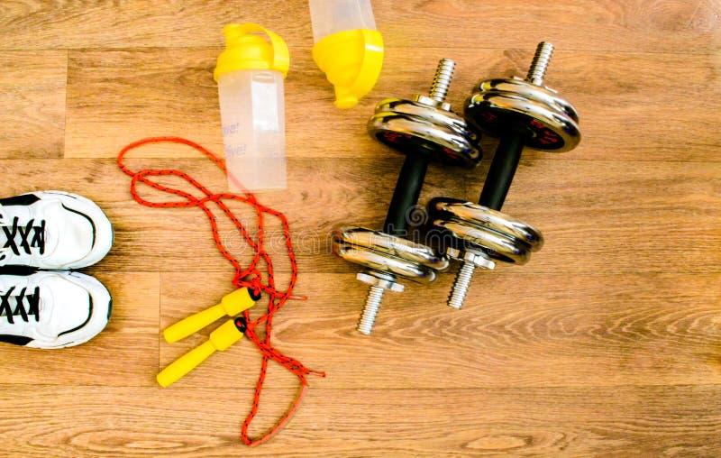 Attrezzatura di sport, corda, forma fisica, palla, sport, asciugamano, scarpe da tennis, pavimento di legno, scarpe da corsa, tes fotografie stock