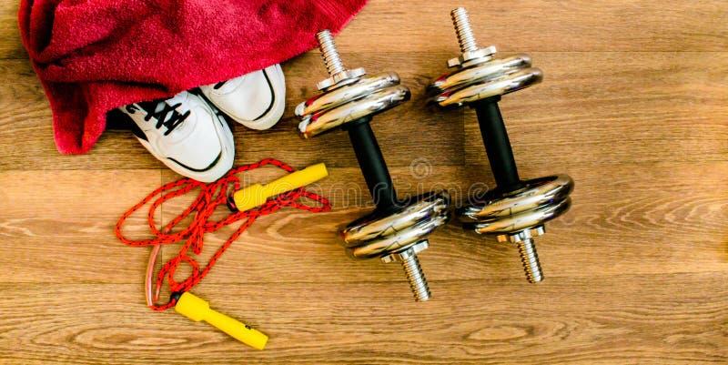 Attrezzatura di sport, corda, forma fisica, palla, sport, asciugamano, scarpe da tennis, pavimento di legno, scarpe da corsa, tes fotografia stock
