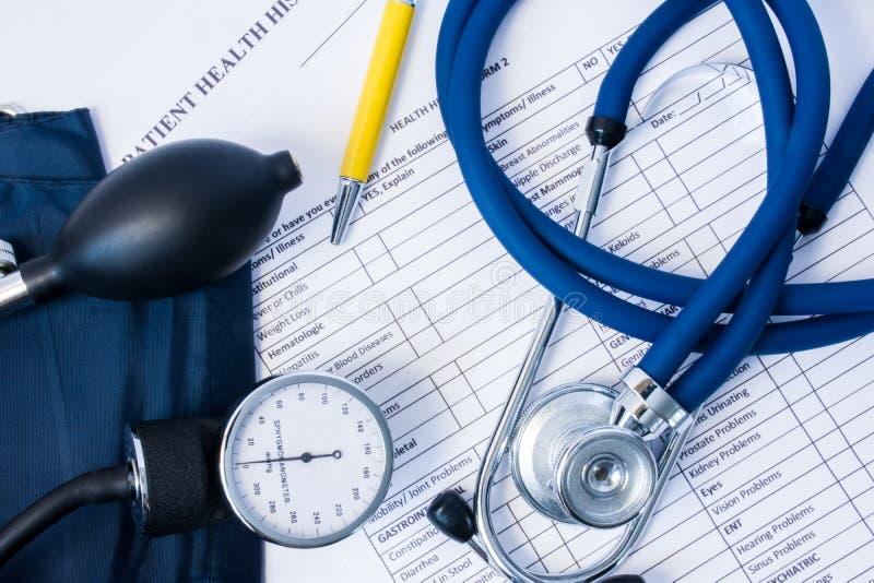 Attrezzatura diagnostica - stetoscopio, calibro di pressione sanguigna che si trovano sulla storia paziente di salute e questiona immagini stock libere da diritti