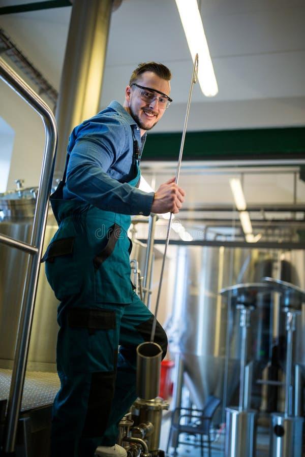 Attrezzatura funzionante della tenuta felice del fabbricante di birra fotografia stock libera da diritti
